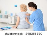 female orthopedist examining... | Shutterstock . vector #648355930