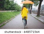 woman in raincoat riding...   Shutterstock . vector #648571564