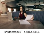 Small photo of Beautiful experienced asian employee analyzing information from internet on netbook while working with accounting data on papers.Good looking woman sitting in comfortable cafe