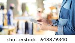 hand using tablet over blur... | Shutterstock . vector #648879340