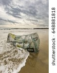 Small photo of A beat up lobster trap is washed ashore in Salisbury, MA.