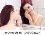 young woman removing makeup in... | Shutterstock . vector #649093624