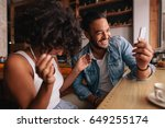 smiling young couple sitting at ... | Shutterstock . vector #649255174