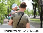 Small photo of Middle-aged man carrying his crying toddler son during their walk in the park, bad mood, negative emotion, upbringing and family concept, summer outdoor