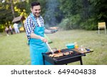 handsome man preparing barbecue | Shutterstock . vector #649404838