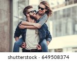 Small photo of Beautiful young couple in sun glasses looking at each other and smiling while standing outdoors. Girl piggyback