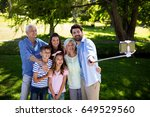 Small photo of Multi generation family taking a selfie with selfie stick in park