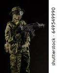 Small photo of Portrait of armed woman with camouflage. Young female airsoft sniper observe with firearm. Soldier with gun in war, black background. Military, army people concept