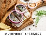 Stock photo sandwich with salted herring butter and red onion on old rustic cutting board selective focus 649552873