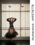 Small photo of Beautiful female ballet dancer in black elegantly posing at the wall barre on a tiptoe in a dance class. Vertical artistic sunny image
