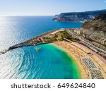 Beautiful aerial view of Playa de Amadores bay with other cliffs on the sea shore on the Gran Canaria island in Spain. Gorgeous sea shore of the island.