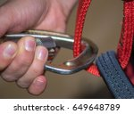 Hand attaches carabiner to a climbing harness  close-up - stock photo