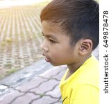 Small photo of Asian Thai child boy absent-minded in the park