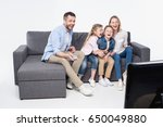 family sitting on sofa while... | Shutterstock . vector #650049880