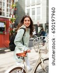 Small photo of Closeup woman riding vintage bicycle in the city center. Activity and healthy lifestyle and environmentally friendly transport