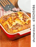 Small photo of Baked polenta with eggs, sausage and fontina in a heat resistant baking dish on a wooden serving board with a metal spatula,and a round white bowl