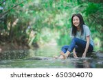 young girl playing water stream | Shutterstock . vector #650304070