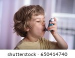 boy using asthma inhaler to