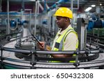 Small photo of Factory worker using a digital tablet near the production line in factory