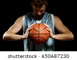 Small photo of Basketball player concentrating on game. Young bearded man in blue tank top holding a ball with both hands on black background.