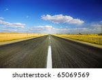 Long road travelling through a autumn field - stock photo