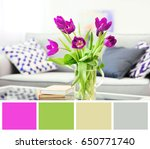 Small photo of Lilac color accent in modern interior. Bouquet of tulips in vase on table
