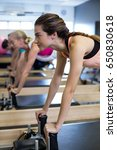 Small photo of Determined women practicing stretching exercise on reformer in gym