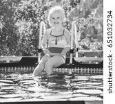 Small photo of Fun weekend alfresco. smiling healthy girl in colorful swimsuit sitting in the swimming pool