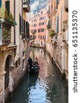 Small photo of the many canals of Venice to play the role of city streets/view of Venetian canal with a gondola and a gondolier on a Sunny day