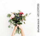 Small photo of Girl's hands holding beautiful flowers bouquet: bombastic roses, blue eringium, eucalyptus, isolated on white background. Flat lay, top view. Floral composition