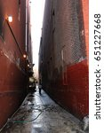 Small photo of dark alleyway between old tall brick wall building in city