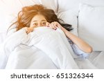 smiling young asian girl in bed ... | Shutterstock . vector #651326344