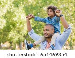 father giving son ride on back... | Shutterstock . vector #651469354