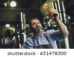 Male Brewery Worker Examining...