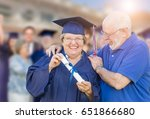 Small photo of Senior Adult Woman In Cap and Gown Being Congratulated By Husband At Outdoor Graduation Ceremony.