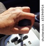 Small photo of Hand using gear stick, inferior of car.