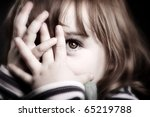 Stock photo a gorgeous little girl playing peekaboo and peering through her fingers adorable 65219788