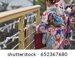 Stock photo japanese woman in kimono reading o mikuji fortune prediction strips of paper at shinto shrines 652367680