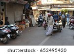 Small photo of Mumbai, India - October 11, 2015: Old Muslim man of Dawoodi Bohra sect wearing turban in traditional dresses pulling goods cart at Chor Bazaar thief market