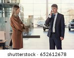Small photo of girl buying a car or renting a car tensely looks at the seller of a man in a suit who solves the problem over the phone. Against the backdrop of the car dealer and panoramic windows.