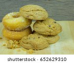 Small photo of Donus and chocolate chip cookies. Cookies on wooden background.