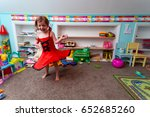 Small photo of One Caucasian Child Plays Alone While Dancing In Her Suburban Home Play Room