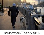 A Man Walking With His Dog And...
