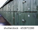 A Row Of Green Boat Sheds With...