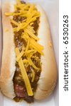A Hot Dog Topped With Chili An...