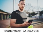 Small photo of Workout outdoor lifestyle concept.Young man stretching his arm muscles before training.Bearded Muscular athlete using smartphone and exercising outside in sunny park. Blurred background