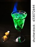 Small photo of Blazing absinthe with sugar pieces on special spoon. Vertical studio shot.