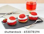 Small photo of French Cakes with strawberry cream shanti. aery brewing cake on black shale. Restaurant composition on white background.
