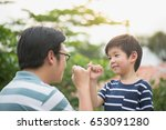 asian father and his son making ... | Shutterstock . vector #653091280