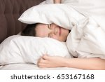 woman lying in bed covering...